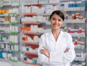 Portrait of a pharmacist working at the drugstore and looking at the camera smiling