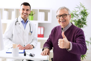 Satisfied old patient with success young doctor in office