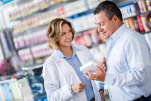 Man at the drugstore asking pharmacist for advice about some medicine